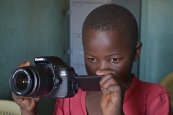 A child from Mathare Foundation reviews a photo he took